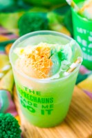 """St. Patrick's Day Punch in a plastic cup that says """"the leprechaun's made me do it""""."""