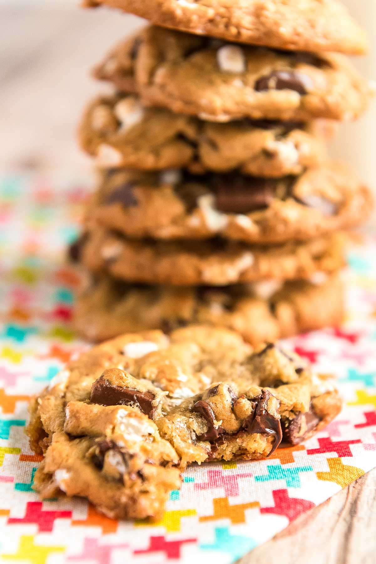 Stack of cookies with one cookie in the foreground with a bite taken out of it.