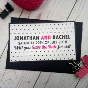 Polka Dot Save The Date with matching black envelope. Black polka dot and black and pink writing.