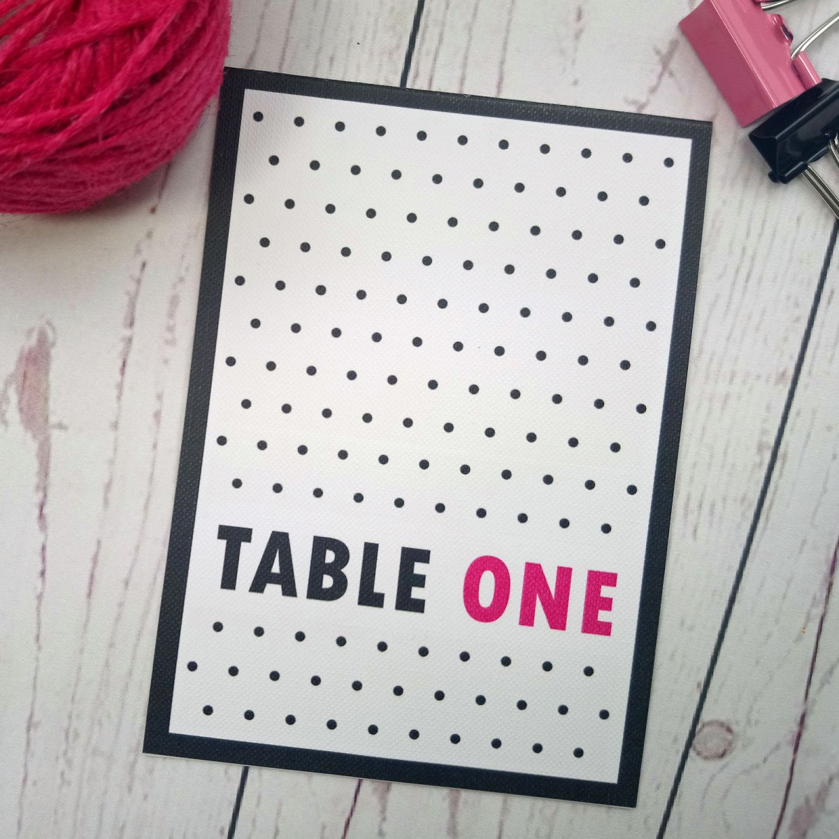 Polka Dot Table number on white textured card in black and pink with polka dots.