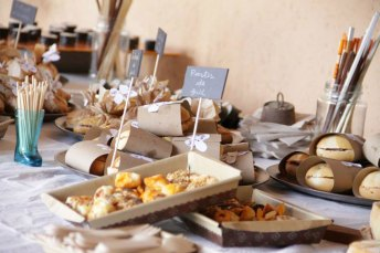 Savory table full of snacks and sandwiches in trays for wedding guests