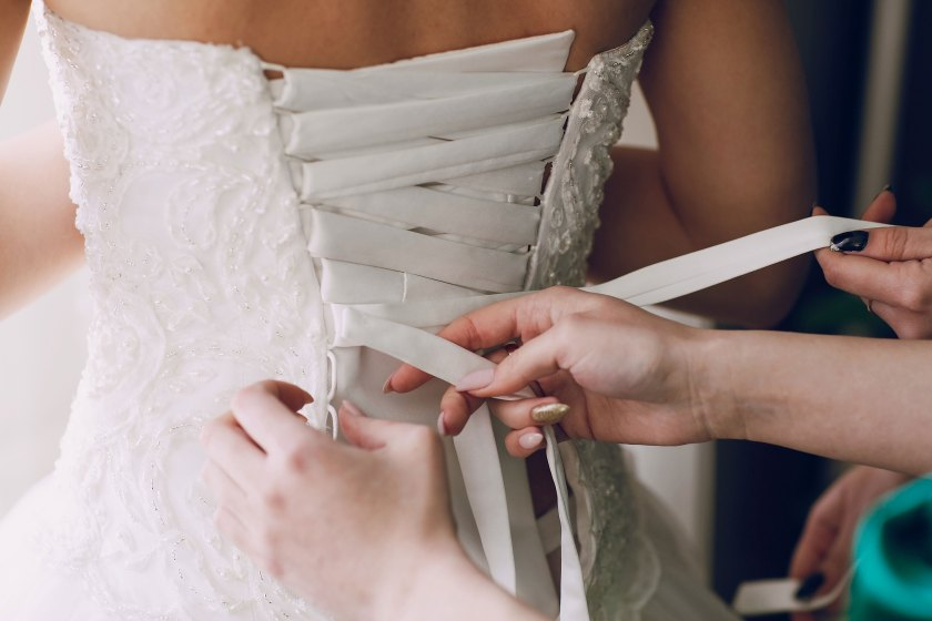 bride getting wedding dress fitted