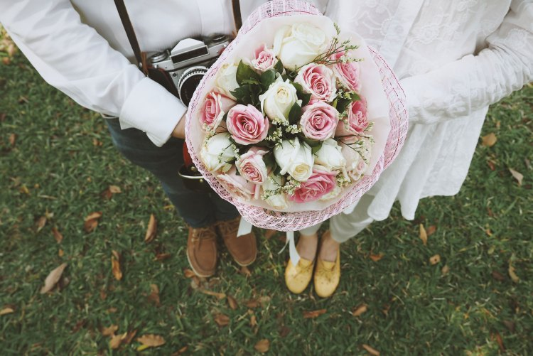 modern bride and groom holding a pink and white rose flower bouquet