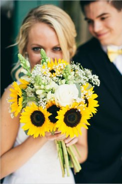 Bride hiding behind sunflower bouquet