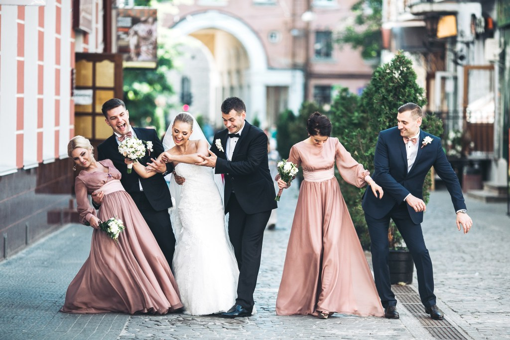 bride, groom, bridesmaids and best men dancing on the street