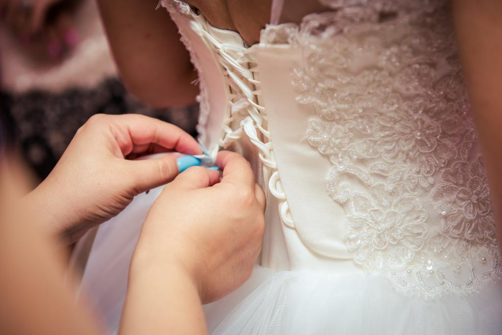 Photo of seamstress fixing brides white wedding dress