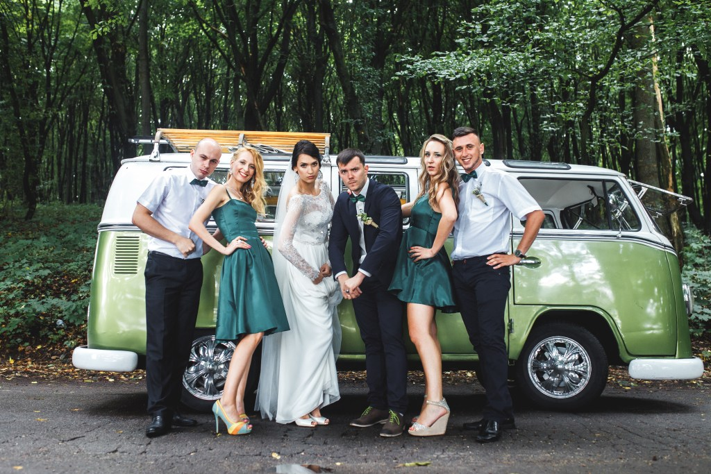 bride, groom, bridesmaids and best men posing in front of a vintage green campervan