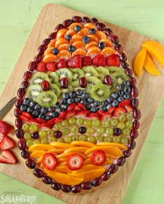 Easter Egg Fruit Pizza - Fruit pizza displayed on a cutting board. | From SugarHero.com