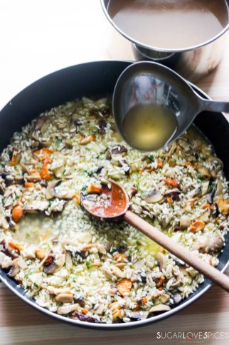 Mixed Mushroom Risotto-ladle of broth in the pan