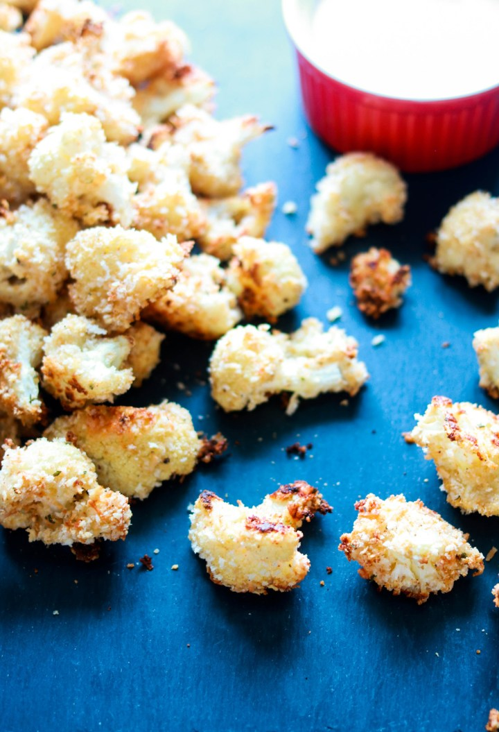 panko and asiago crusted popcorn cauliflower-closeup-on a board-sauce in background