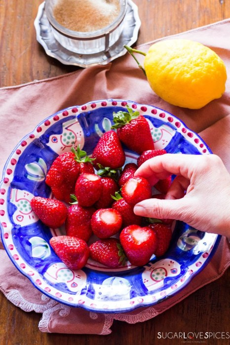Strawberries with sugar and lemon-removing the top