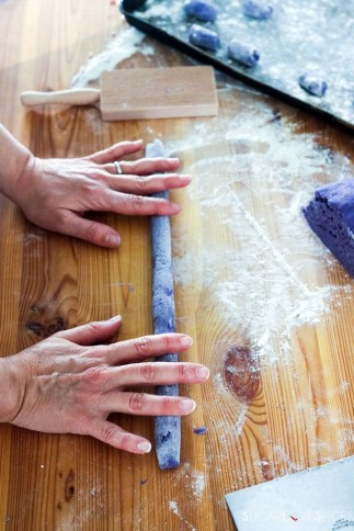 Homemade purple potato gnocchi-rolling gnocchi dough with hands on wood board