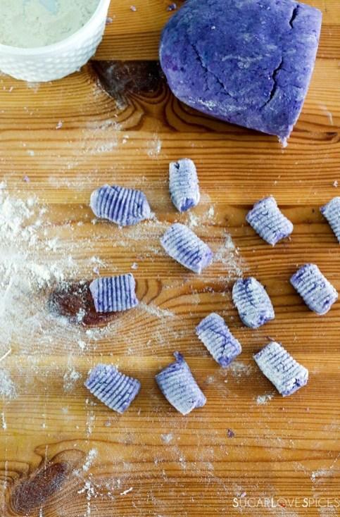 Homemade purple potato gnocchi-some gnocchi and gnocchi dough on wood board