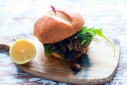 Steak sandwich-feature-on a wood board with lemon on the side