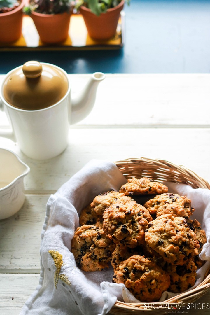 Loaded oatmeal spelt cookies-in a basket-teapot and vases behind