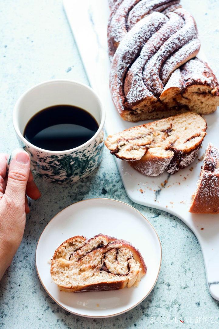 Nutella Pain Brioche Braid-a slice on a plate-hand on coffee mug