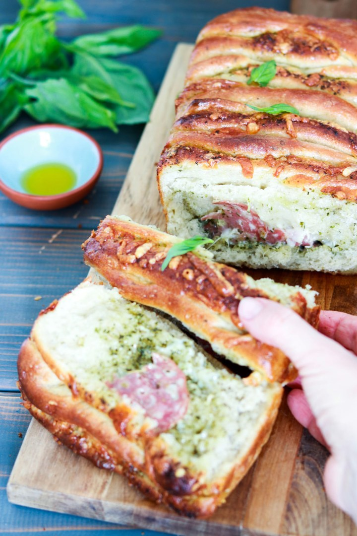Pesto and Salami Pull-Apart Bread-hand pulling a piece apart