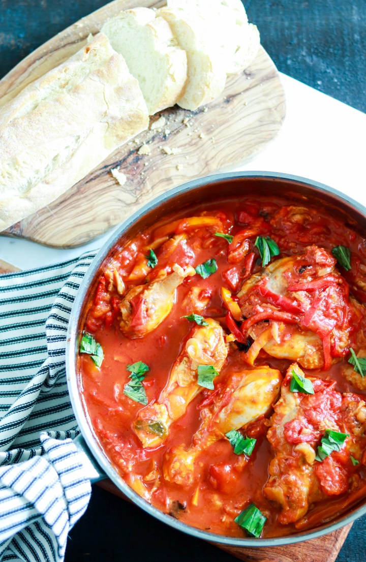 Roman-style Pollo coi Peperoni (Chicken with Peppers and Tomatoes)-in the pan with spoon-bread in background