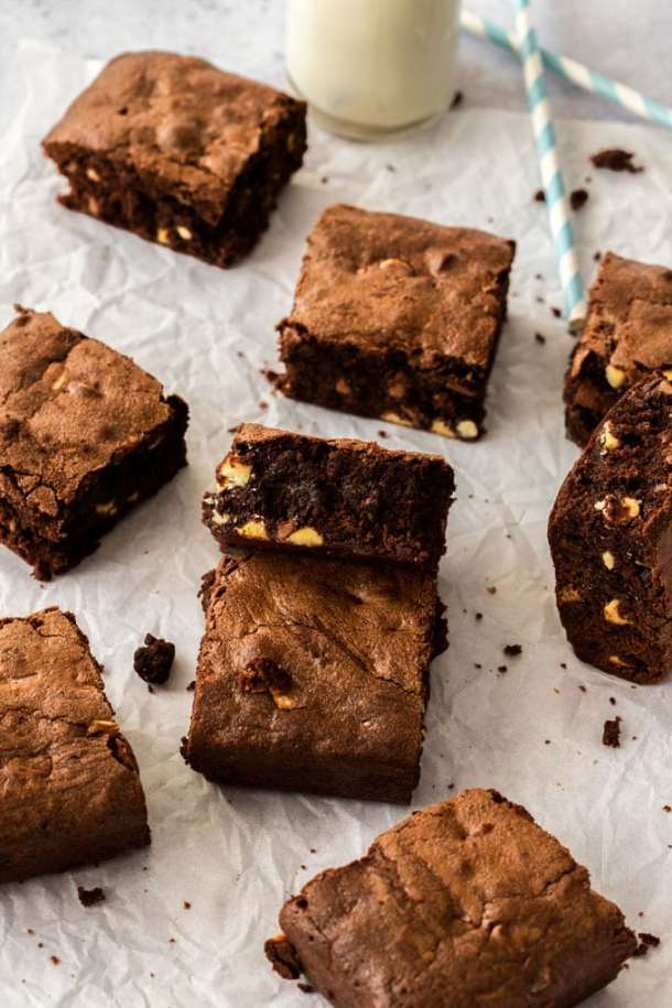 A batch of chocolate chip brownies on a sheet of baking paper with a bottle of milk at the back