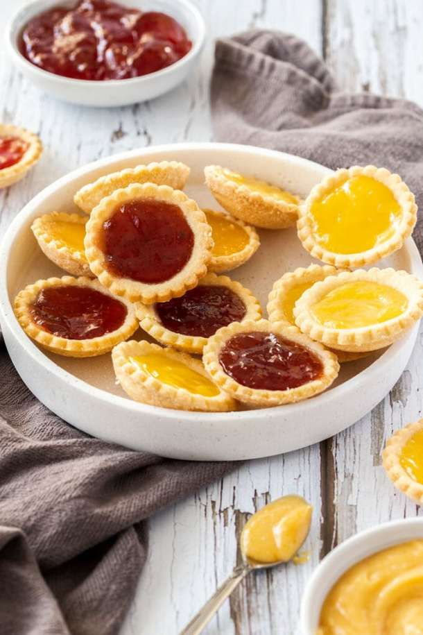 A white platter filled with jam tarts on a dark grey tea towel. It sits on a white wooden background