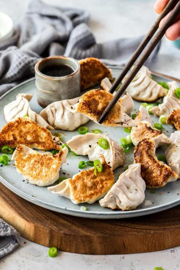 16 pork gyoza on a grey plate with chopsticks picking one up. A small grey pot of sauce behind