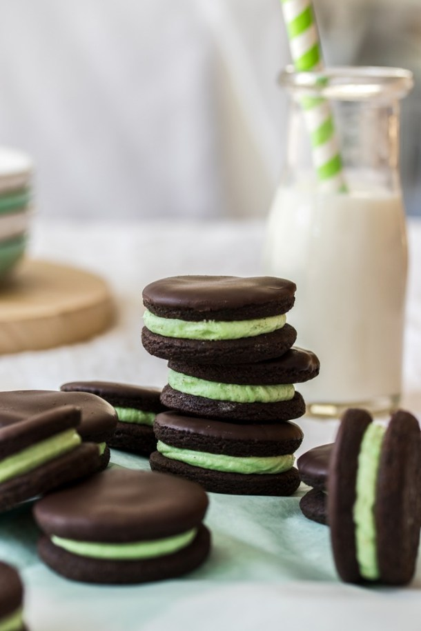 A stack of 3 chocolate cookies filled with green buttercream with a bottle of milk in the background
