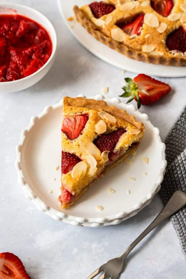 Birdseye view of a slice of strawberry tart on a white dessert plate with a dessert fork in front.