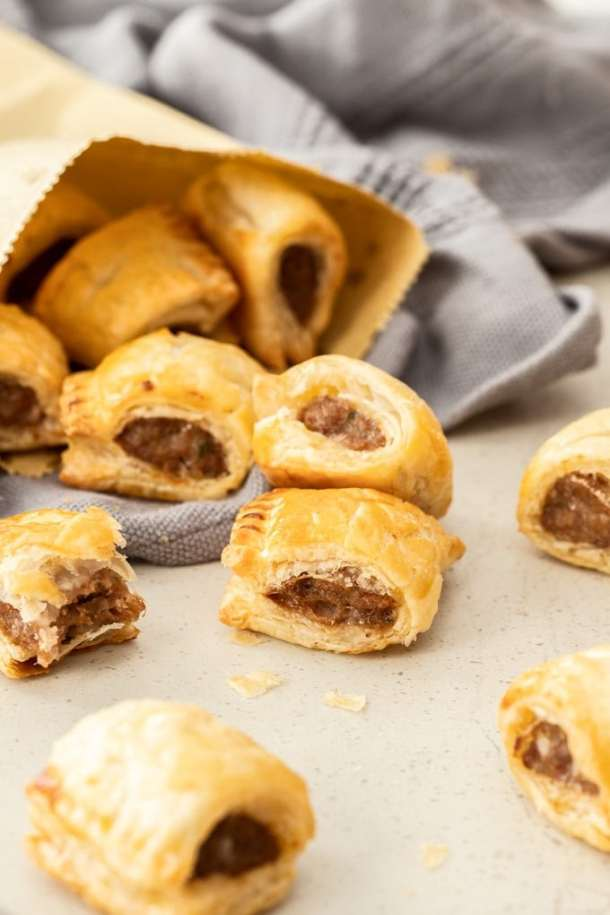Mini homemade sausage rolls tumbling out of a browne paper bag