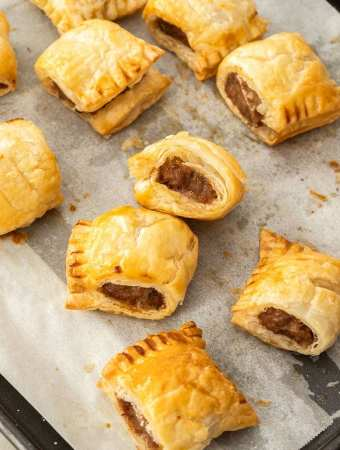 Freshly baked homemade sausage rolls on a baking tray