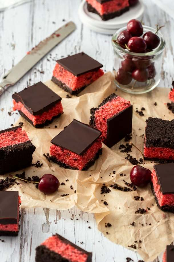 9 randomly placed cherry ripe slices on a piece of brown parchment paper, a glass of cherries at the back
