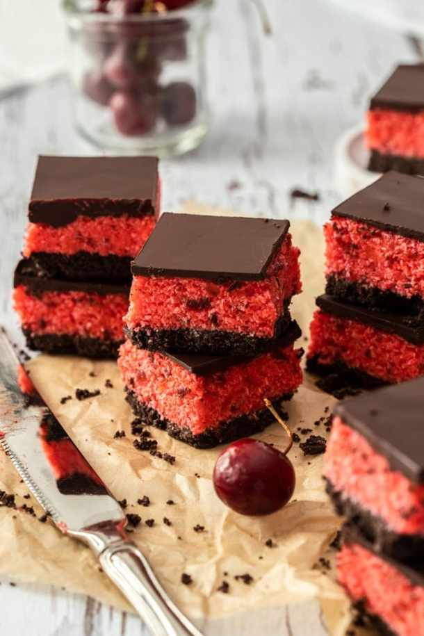 Stacks of cherry ripe slice on brown parchment paper, with a knife in front and a glass of cherries as the back