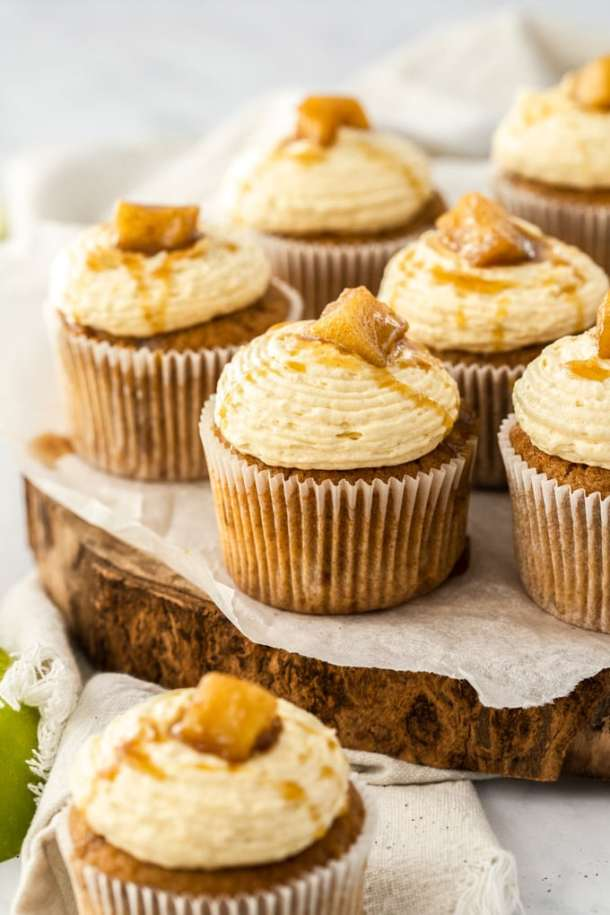 Apple pie cupcakes sitting on a wooden cake board