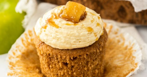 A closeup of an apple pie cupcake with the paper peeled away showing the texture of the cake.