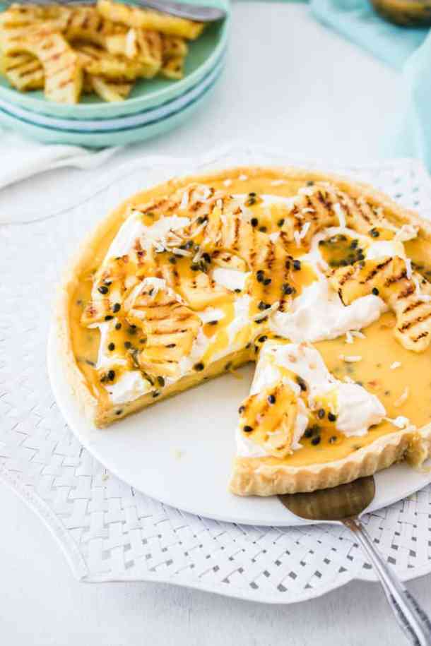 This Passionfruit Tart is a simple passionfruit curd custard filling in a crisp tart shell. It's all topped with grilled pineapple slices and coconut. Tropical tart heaven.