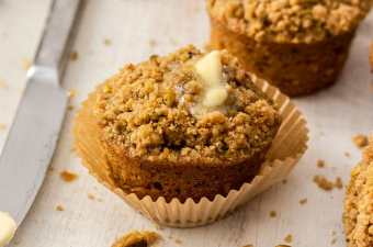 A closeup of a muffin topped with butter. Knife next to it.