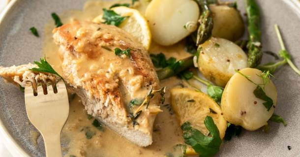 A closeup of a cooked chicken breast in a creamy sauce with potatoes