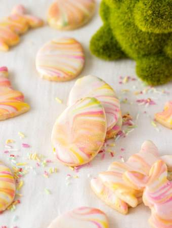 Iced sugar cookies stacked against each other surrounded by sprinkles