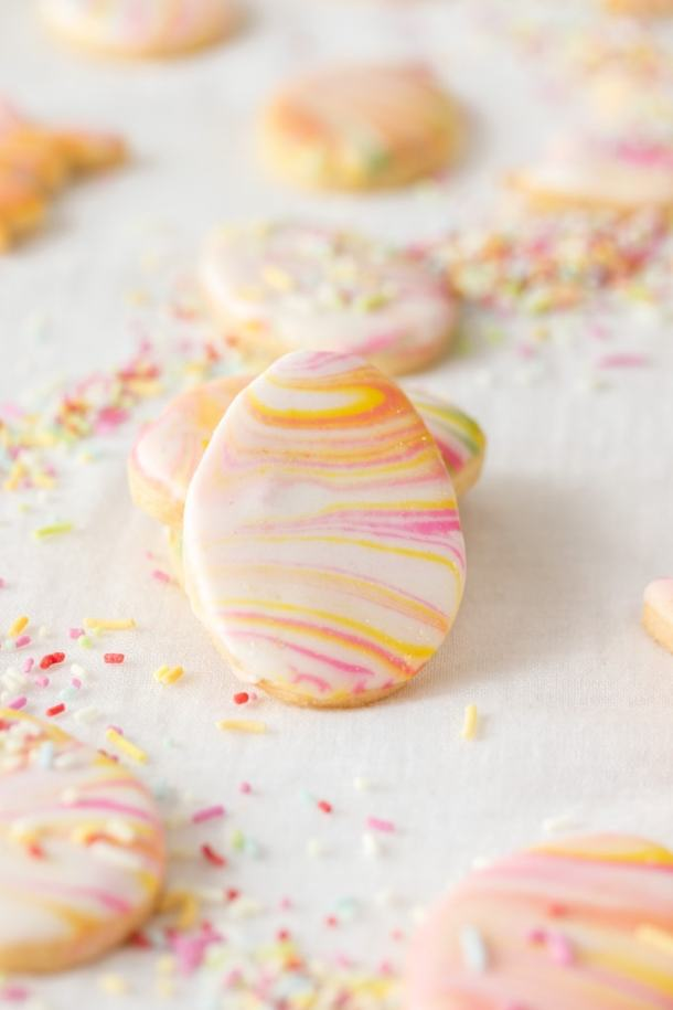 A closeup of an iced sugar cookie with more in the background
