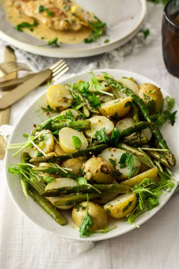 Potato asparagus salad on a white plate with gold cutlery