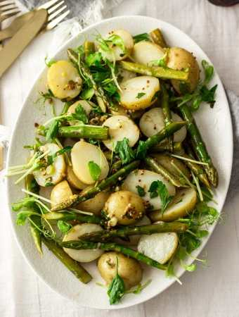 Birdseye view of potato asparagus salad on a white plate