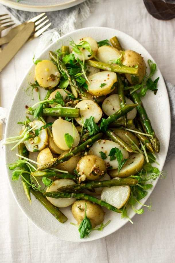 Birdseye view of potato asparagus salad on a white plate