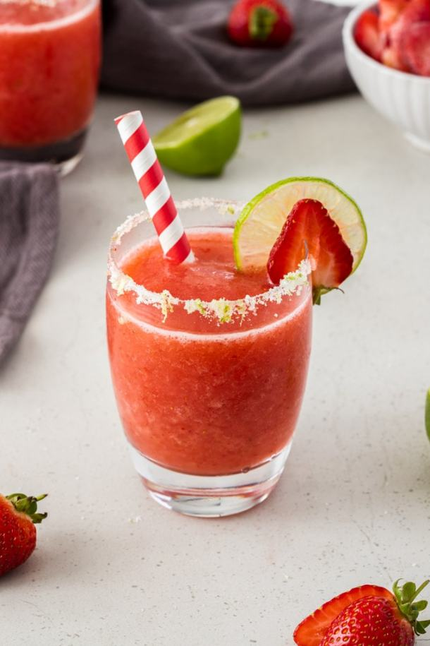 A single glass of frozen strawberry daiquiri with a slice of lime and strawberry