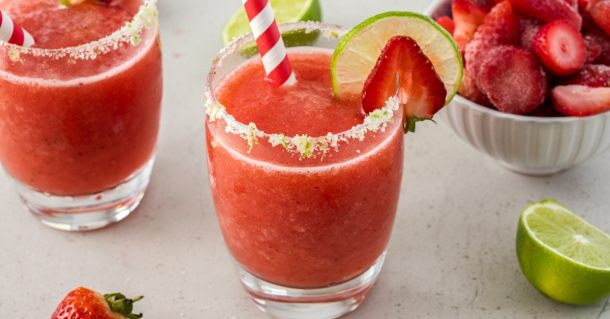 Two frozen strawberry daiquiri cocktails sitting next to each other