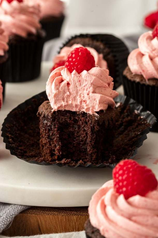 A chocolate cupcake with raspberry frosting with a bite taken out of it