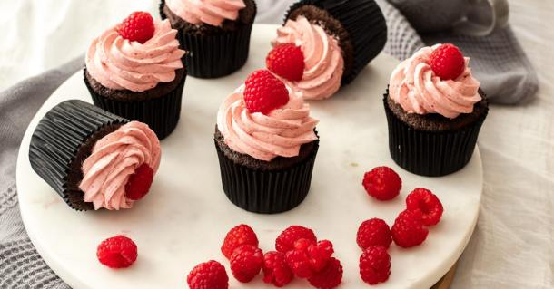 Chocolate cupcakes with raspberry frosting sitting on a white platter with raspberries in front