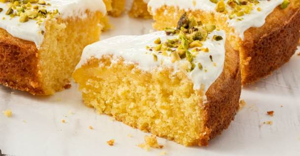 Close up of a slice of cake topped with yoghurt and pistachios
