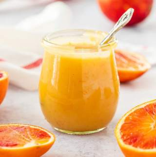 A glass jar filled with orange curd. A spoon sticking out of it. It is surrounded by sliced blood oranges on a concrete background