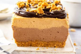 Front on view of the inside of a square slice of peanut butter cheesecake. it sits on a white board with a spoon of ganache in front