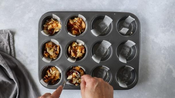 Spoonfuls of florentine biscuits mixture being put into a muffin tray