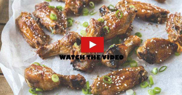 A group of sticky asian chicken wings on a sheet of baking paper with spring onions sprinkled over them. There is a video play button overlay
